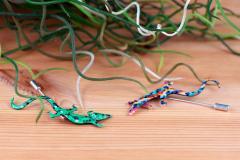 Fotografía de un conjunto de salamandras en colores variados con el sello de Artesanía de Galicia, realizados en papel extra resistente.