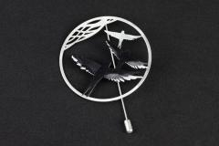 Front view of a needle hoop pin, with carved bird silhouettes and black paper pieces modelled and set with 3D effect.
