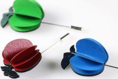 Three apple brooches in blue, red and green