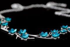Plano detalle de pequeñas florecillas de papel en tonos azules que se engastan a un original collar con base troquelada en forma de hermosas ramas de metal.