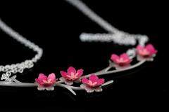 Vista detalle de colgante en forma de rama plateada con flores de almendro 3D de capas de papel rosa engastadas y cadena de eslabones desenfocada.