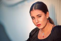 Mujer que luce un original collar largo con cadena fina plateada y colgante circular de inspiración cubista con labios de papel de color rojo engastados.