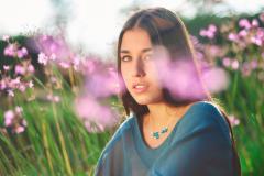 Mujer joven de perfil luciendo una elegante gargantilla de pequeñas flores de almendro azules, engastadas en un colgante fino con ramas plateadas.