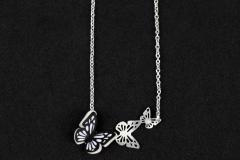 Necklace with a black paper butterfly mounted on a silver base with three butterflies flying, carved and attached to a chain of links.