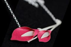 Detailed view of two pink paper lilies set to a base of die-cut branches and a thin silver chain in a semi-focused shot.