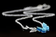 Detail of blue paper craft wings, semi-open on one of the three pieces of butterflies carved in silver necklace with chain in unfocused view.