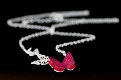 Detail view of a pink paper butterfly with modeled and semi unfolded wings, attached to a silver base and chain in a blurred plane.