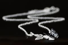 Foreground of silver necklace with silhouettes of three carved butterflies, overlapping wings of black die-cut paper and chain in unfocused view.