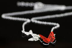 Close-up of necklace with a butterfly embossed in carmine paper, hand-set on a silver base and link chain.