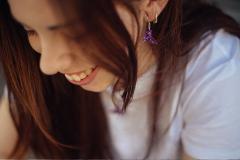 Chica feliz con pendientes originales de pajarita en papel