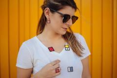 Model with necklace and earrings with geometric shapes of colors. Mounted on silver.