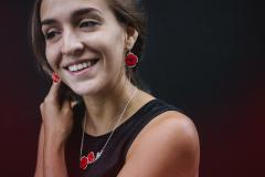 Woman with paper craft accessories. Two earrings with hardened paper poppy flowers, assembled with 3D effect on a silver base.