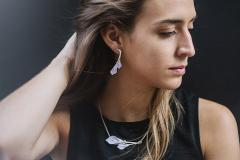Close-up of a young woman in profile wearing a silver earring with carved branches and two paper calla lilies set with a glossy finish.