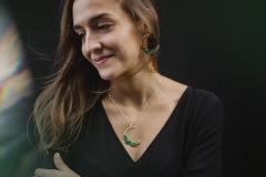 Mujer hermosa luciendo un collar con un semi aro de ramas labradas en la misma pieza, incrustaciones de pétalos de papel y cadena tipo veneciana.