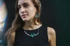 Model featuring a short necklace with two paper birds assembled on a rigid base set to a silver-link chain.