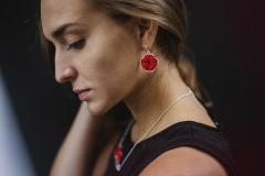 Model with handcrafted jewellery. Poppy flower earring with paper petals and 3D effect on a silver-coloured die-cut base.
