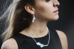 Model with an inverted design semi-long earring with two paper calla lilies set in a rigid silver base with branches and hidden closure.