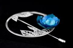 Brooch with a needle lock, carved in the shape of a ring and small leaves on which a camellia with paper petals in a range of blues is set.