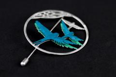 Detailed shot of a silver-based, ring-shaped pin with two turquoise paper birds assembled with 3D effect.
