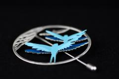 Circular silver needle pin with detail view of two paper birds in blue tones that are set to the base with 3D effect.