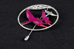Side view of silver ring-shaped brooch with bird filigree details and mauve paper wings with glossy finish.