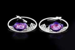 Detail view of two earrings with lilac camellias in glossy paper, mounted on a hoop of carved leaves and silver hook closure.
