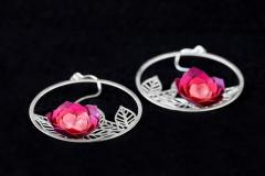 Side view of a pair of pink paper camellia flower earrings, mounted on filigree leaves hoops and sterling silver clasps.