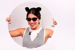 Chica joven sonriente con orejas de gato y divertidos pendientes de papel con forma de minino negro.