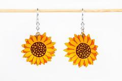 Vista frontal de dos zarcillos con cierre fino de gancho y engastes de flores de girasol elaborados con capas de papel endurecido de color amarillo.