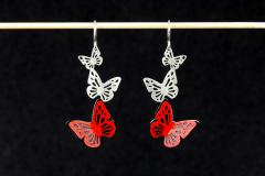 Front view of earrings with silver hook clasps and two butterflies made of hardened carmine paper, set to the carved silhouette at the base.