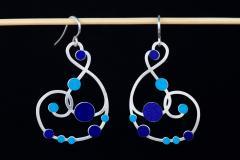 Vista frontal de aretes plateados con cierres de gancho y diseño de trazos ondulantes recorrido con incrustaciones de círculos de papel en tonos azules.