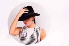 Bella mujer con sombrero y pendientes Frenchy de origami engarzados en plata de ley.