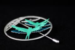 Side view of silver needle brooch with filigree ring and green paper bird settings with spread wings, modelled with 3D effect.