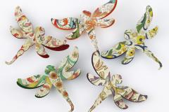 Various paper jewelry brooches in the shape of a dragonfly.