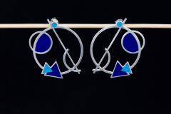 Un par de zarcillos plateados con base de aro vaciado y composición geométrica de triángulos y círculos con engastes de papel azul y cierres a presión.